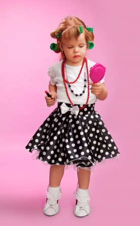 Little fashion-conscious girl, just like mother - using  lipstick, mirror, rollers and others photo