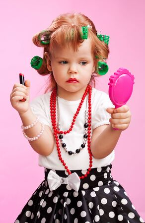 Little beautiful girl playing to be a big sister, with using  lipstick, mirror, rollers and others photo