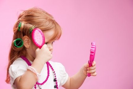 three year old: Little girl playing a hairdresser brushing her hair and looking in the window