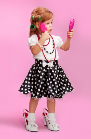 Little girl pretending to be big standing in mothers shoes, hair rollers and brush and looking at the mirror photo