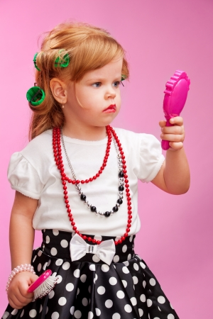 Little girl playing a hairdresser holding hair brush and mirror as well as using rollers photo