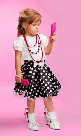Little girl playing to be her bigger sister standing in adult woman's shoes and using hair  brush and rollers photo