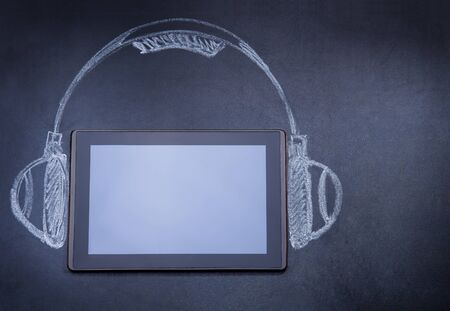 Tablet computer as audio player on the blackboard with tripod and strobe drawn with chalk photo
