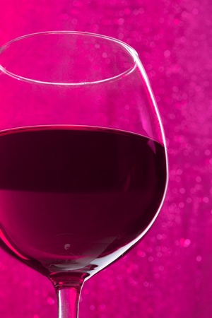 Glass of wine on sparkling purple background photo