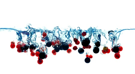 Lots of currants red and white berries falling into water isolate on white photo