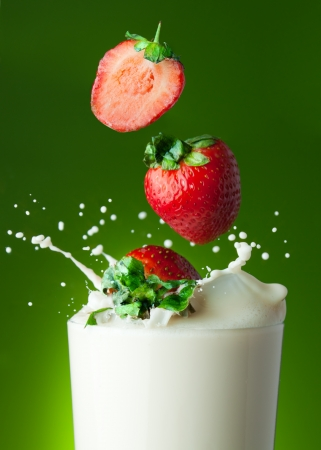 Strawberry cocktail allegory - berries falling into the glass with milk with splashes photo