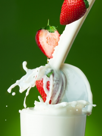 Filling the glass with milk with strawberry photo