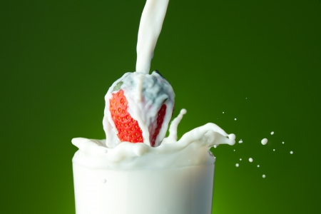 Glass filling with splashing milk and red ripe strawberry on green background photo