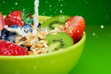 Bowl with muesli and fresh berries and fruits with splashing milk photo