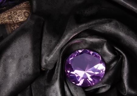 Pink diamond in the black expensive beautiful fabric