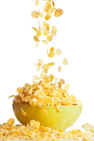 cereales: Volar a los copos de ma�z del taz�n de fuente aislado en blanco