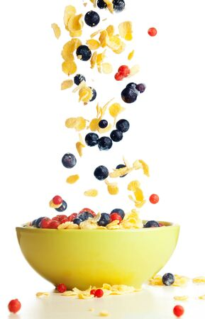 bowl of cereal: Flying to the bowl corn flakes with berries isolate on white