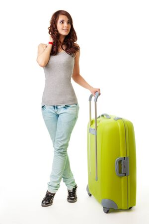 Young woman standing with luggage trolley bag photo