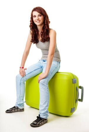 Happy girl sitting on the big green luggage bag photo