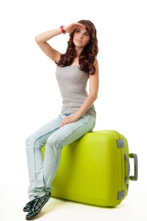 Young woman sit on her luggage bag photo
