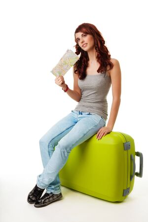 Girl sitting on the big green luggage bag and waiving with map photo