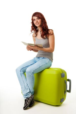 Happy nice smiling woman sitting on the big green bag with map photo