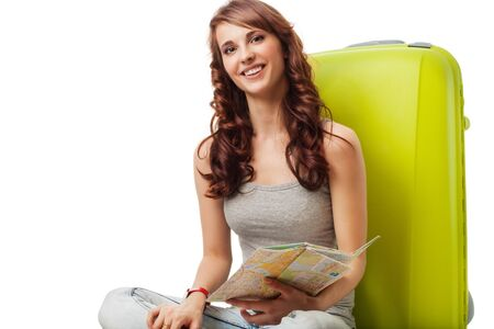 Happy female woman sitting with map and bag waiting photo