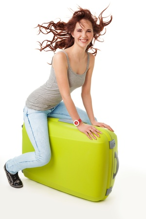 Nice happy girl with flying hair and wide smile rinde a luggage bag photo