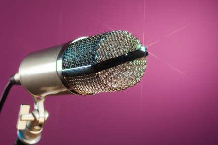 metallic microphone on pink background sparkling photo