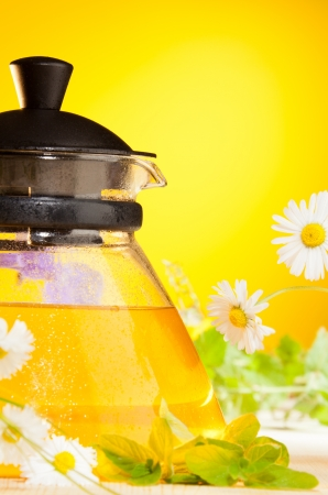 minty: glass teapot with chamomile tea on yellow background Stock Photo