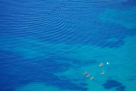 bird eye view: small group of kayaks in crystal clear Adriatic waters