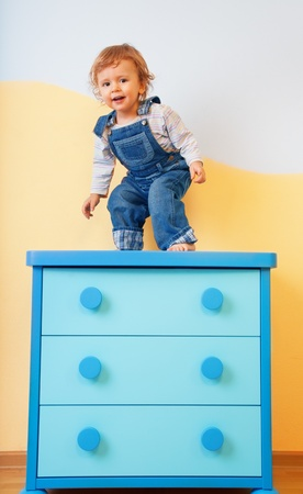 Toddler standing and jumping from furniture Stock Photo