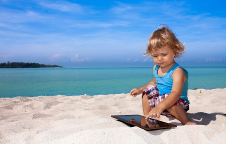 cute blond 2 years old kid playing tablet pc photo