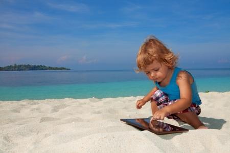 Szczęśliwy dzieciak na plaży gra tablet PC