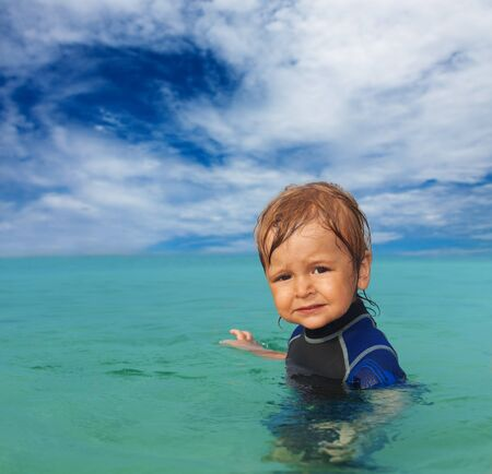 Toddler standing in the water with wandering expression on the face photo