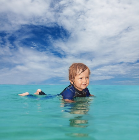 wet suit: Little boy laying in the water wearing a wet suit