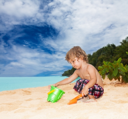 Kid playing on the seashore with shovel and bucket photo