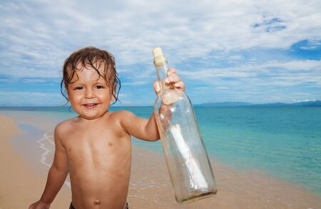 Two years old boy with mayday bottle with message on the beach Stock Photo - 15811554