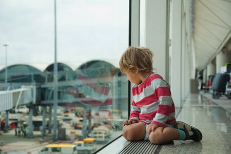 interested baby: little boy looking at window sitting in the airport on the floor and waiting for his flight Stock Photo