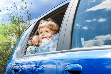 cute little boy traveling in the car and observing nature from open window photo