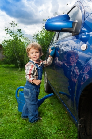2 years old: little boy helping his parents to wash car