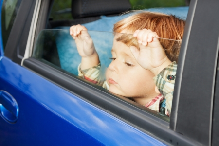 hatchback: little kid is sitting sad on the back sit and look tired of car trip