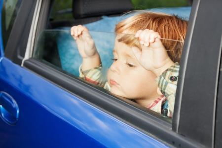 bambini pensierosi: ragazzino triste è seduto sulla schiena sedere e guardare stanco di viaggio in auto Archivio Fotografico