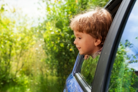 mesmerized: curious funny little kid looking outside of car window