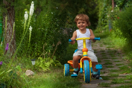 cute child riding his trike in the garden photo