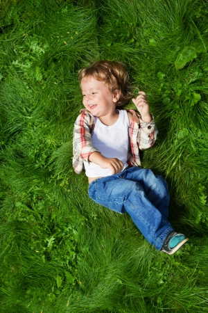 2 years old: cut boy laying on the green grass and rolling