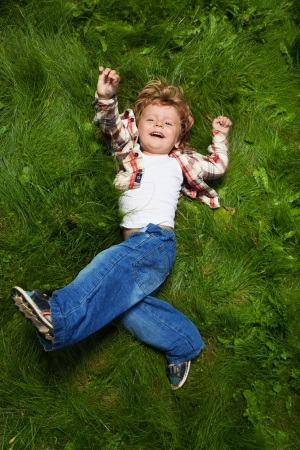 laughing boy rolling on emerald grass photo
