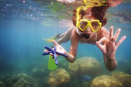 funny snorkeler showing gorgeous starfish Stock Photo - 15860844