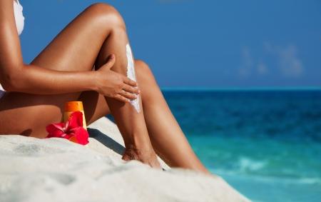 beautiful legs: Woman sitting on the beach and moisturizing her skin