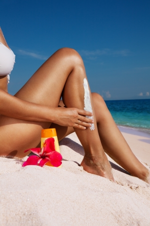 Woman applying sunscreen sitting on the shore photo