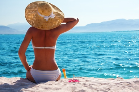 sun protection: woman in white bikini resting on the beach in straw hat