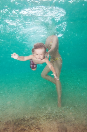 Mother teach little son to swim in the water - underwater shoot photo