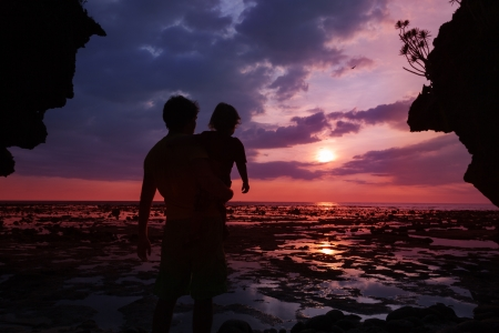 Silhouettes of dad and his kid watching sunset on the seashore photo