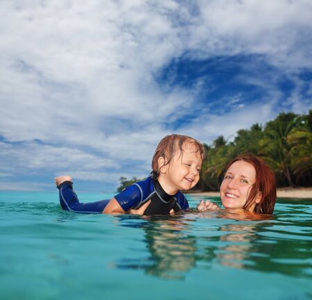 wet suit: Mother teaches little boy to swim in the sea. Two years old boy wears wet suit Stock Photo
