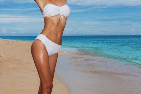 tanned body: Tanned body on the beach in swimsuit near the sea Stock Photo